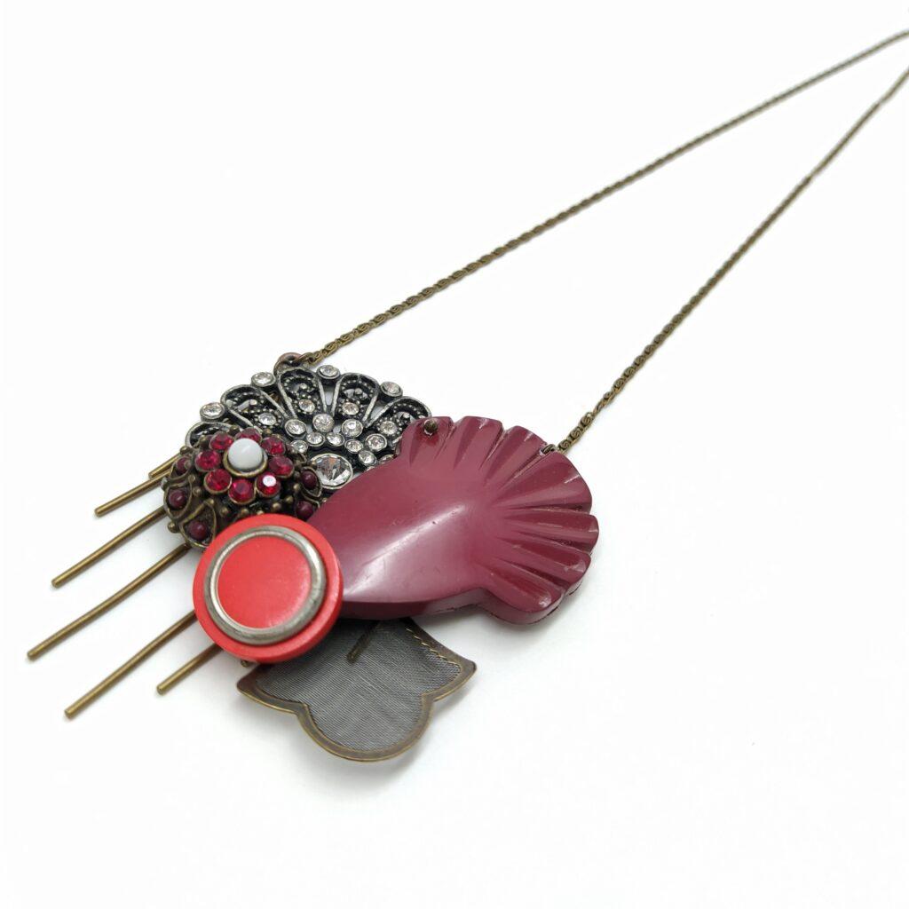 """Sautoir composé de boutons  de boucles d'oreille et d'un élément de boucles de ceinture des années 1980 aux accents Art Déco. Cette composition est montée sur une chaîne bronze """"chemin de fer"""" de longueur 85cm qui peut être réduite sur demande."""