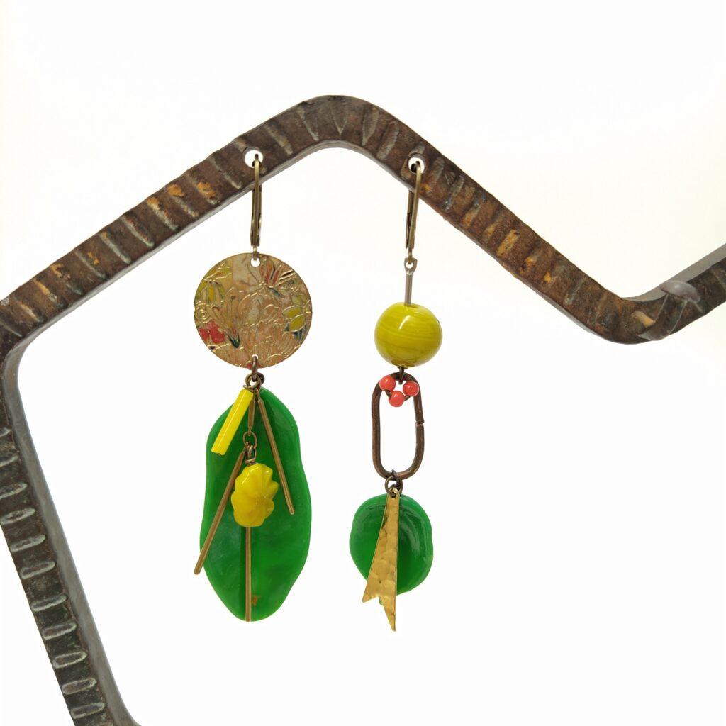 Dormeuses asymétrique en laiton bronze composées  de perles de verre aux provenances diverses  de breloques dorées et de feuilles en verre tchèque artisanalement réalisées dans les années 1930.