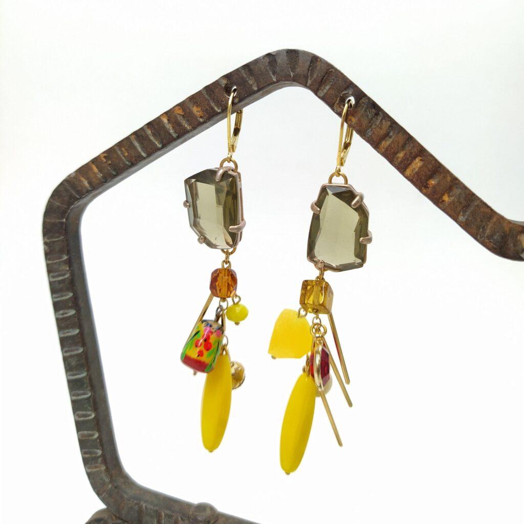 Dormeuses en laiton doré à l'or fin composées d'éléments de collier récent et de chaîne bâton sur laquelle est fixée diverses éléments telles que des perles de verre aux formes diverses et variées dans les tons de jaune et d'ambre ainsi qu'une petite matriochka.