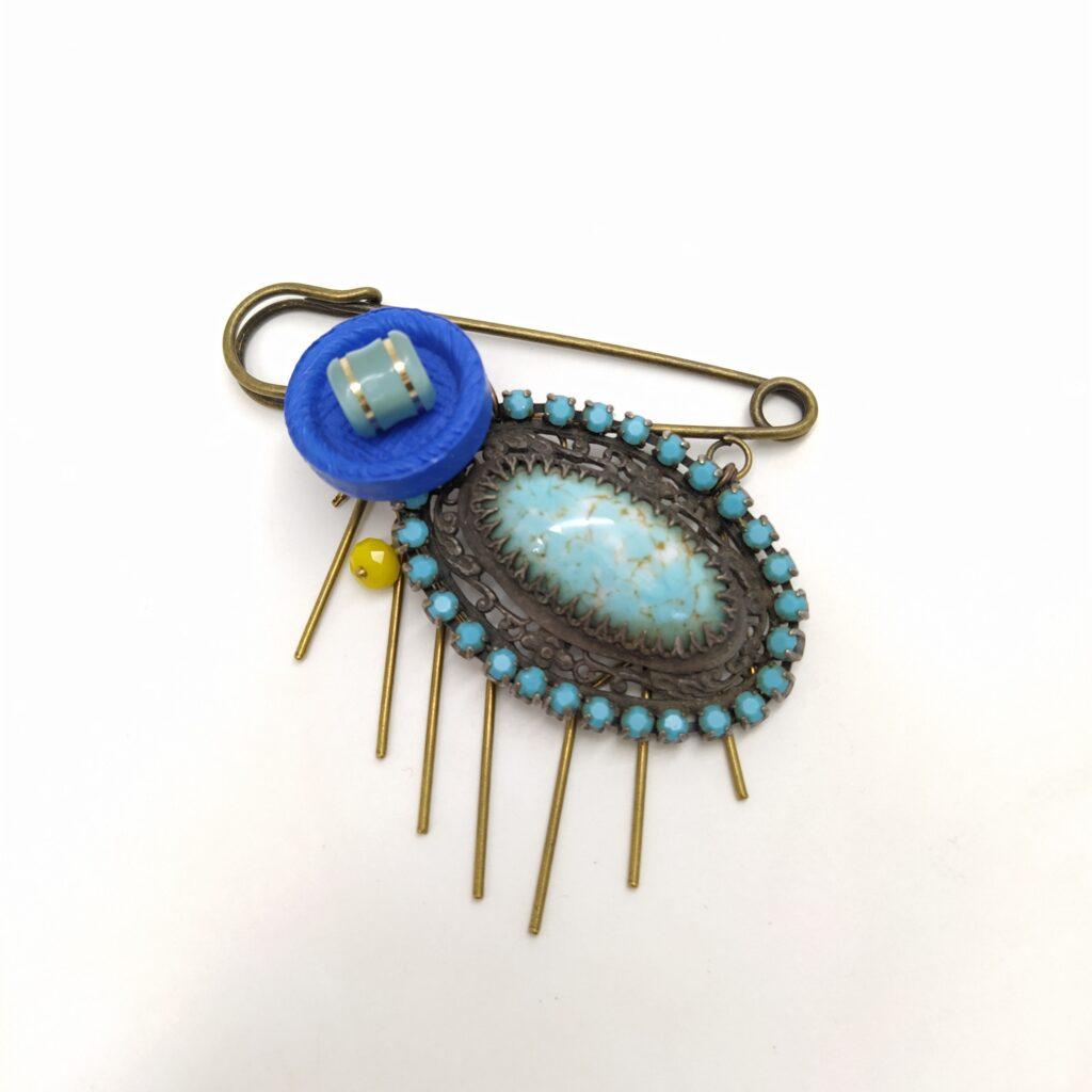 Broche en laiton bronze sur laquelle est fixée une ancienne broche dans les tons turquoise  2 boutons dans les tons de bleu  une perle de verre jaune facettée et de la chaîne bâton bronze.