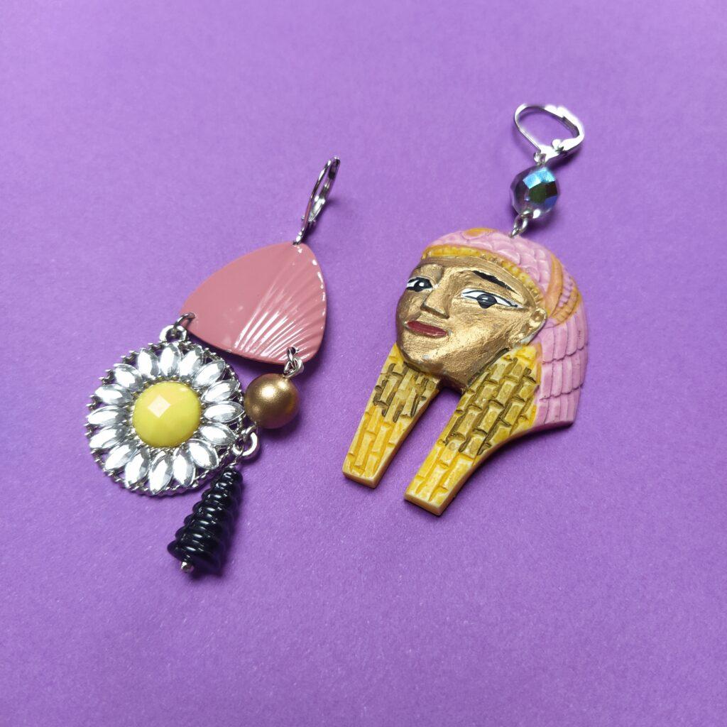 Dormeuses asymétriques en laiton argenté composées d'une pharaonne souvenir d'Egypte  d'une perle de verre facettée  d'une ancienne boucle d'oreille des années 80  d'un élément de collier récent et d'un pompon de verre des années 30.