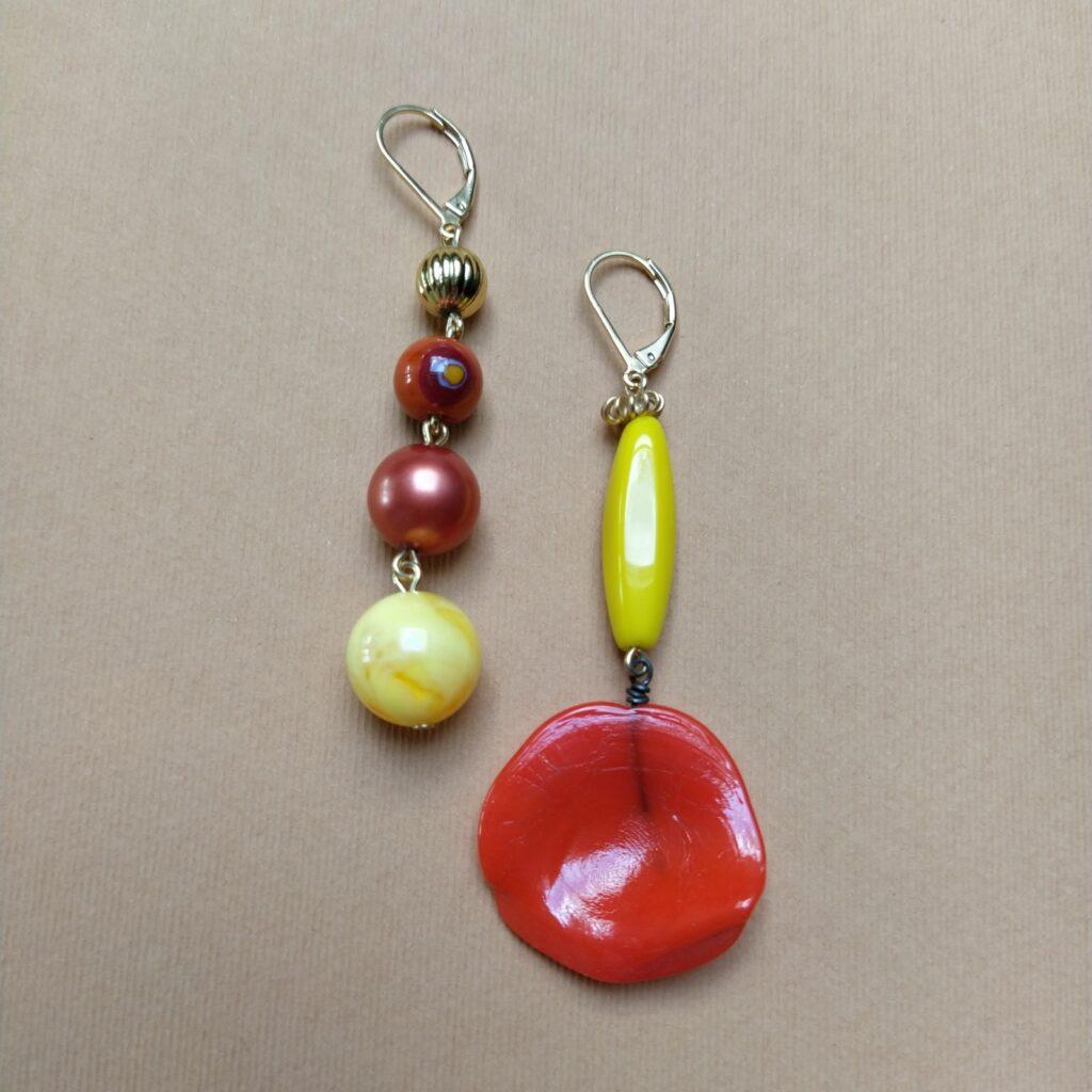 Dormeuses asymétriques en laiton doré à l'or fin composées d'un pétale de verre des années 30 rouge-orangé et de perles au formes et matières diverses dans les tons doré  orange et jaune.