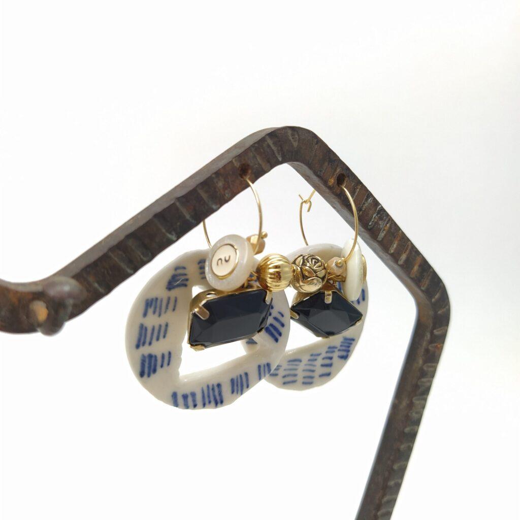 Créoles en laiton doré à l'or fin de 2cm de diamètre composées des créations de Marie Manenc en porcelaine émaillée avec boutons vintage  perles dorées et cabochon noir.